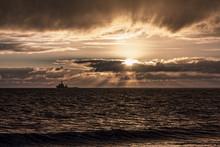 Seascape Sunset. Beautiful Natural Sepia Toned Sunset With A Ship Sailing Across The Horizon.