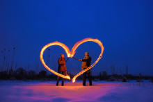 Two Young Lovers Draw Heart Of The Fire On The Valentine's Day.  Snowy Winter Field At Night. Freezelight.