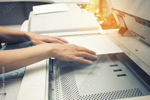 Carta da parati woman hands putting a sheet of paper into a copying device