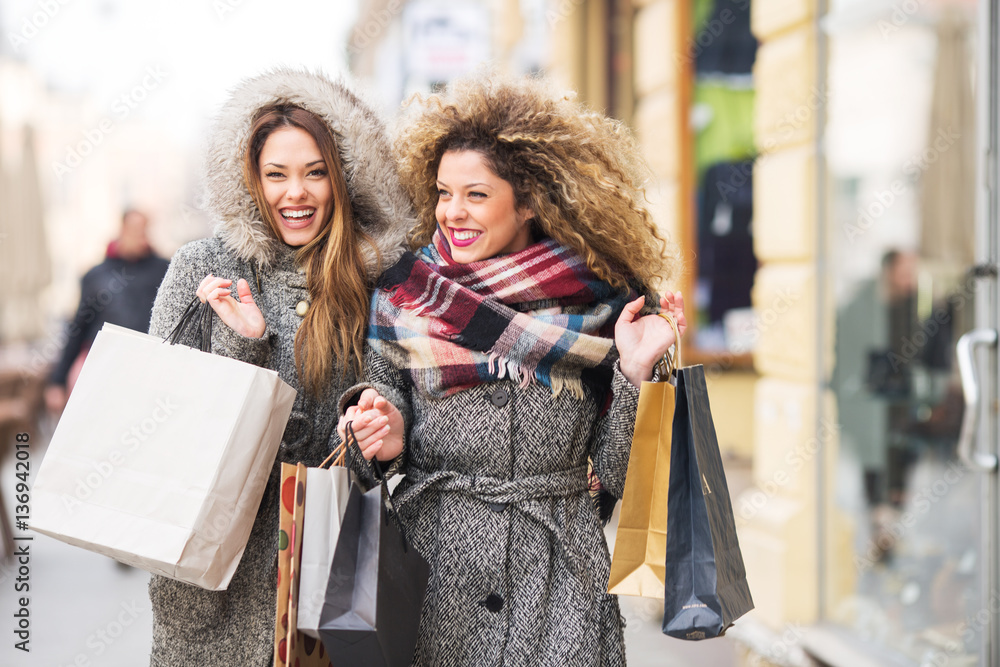 Fototapeta Two attractive smiling young women are shopping in the city