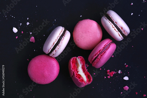 Poster Macarons Macaroons on dark background, colorful french cookies macarons. The broken macarons with crumbs. Gift for Valentine's Day and 8 March International Women's Day