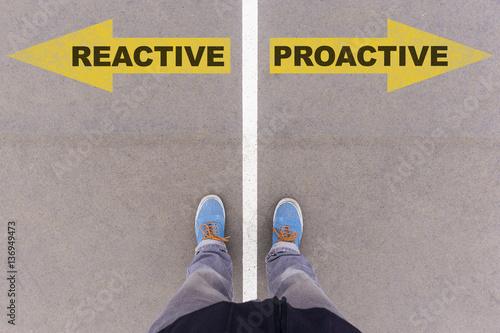 Fotomural  Reactive vs proactive text arrows on asphalt ground, feet and sh
