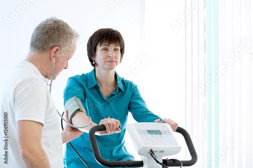 Fotografie, Obraz  Arzt misst Blutdruck bei Patientin die auf dem Ergometer sitzt