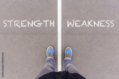 Fotografia  Strength and weakness text on asphalt ground, feet and shoes on