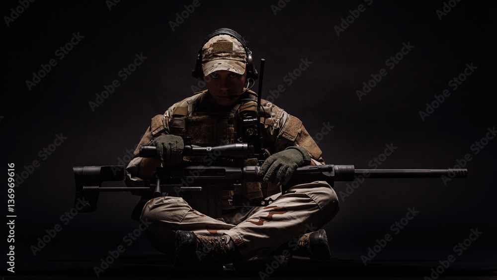 Fototapeta Portrait soldier or private military contractor holding sniper rifle