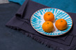 three ripe delicious juicy Mandarin lie in a bright white with a blue plate patterns on fabric cloth kitchen towel on a dark blue black background