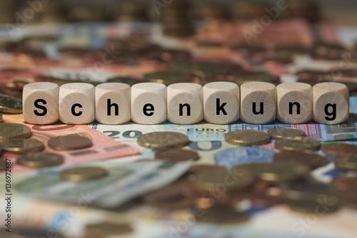 schenkung - Holzwürfel mit Buchstaben im Hintergrund mit Geld, Geldscheine Wallpaper Mural