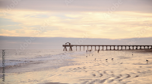 Poster Cote Ocean pier jetty at spectacular sunset. People walking on beach. Peaceful scene, calming waves, pastel cloudy sky, coast. Soft light