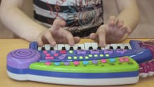 Child Playing On A Toy Pianoforte At Kindergarten. Close-up