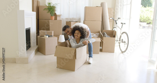 Valokuvatapetti Fun young African woman with an afro hairstyle sitting inside a packing box with her laughing husband behind her as they move into a new home with a stack of packed cartons