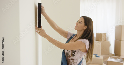 Fotografía  Attractive young woman trying out a placement for a picture on a wall in her new