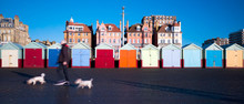 Row Of Colourful Beach Huts, Houses Behind, Man Walking Two With