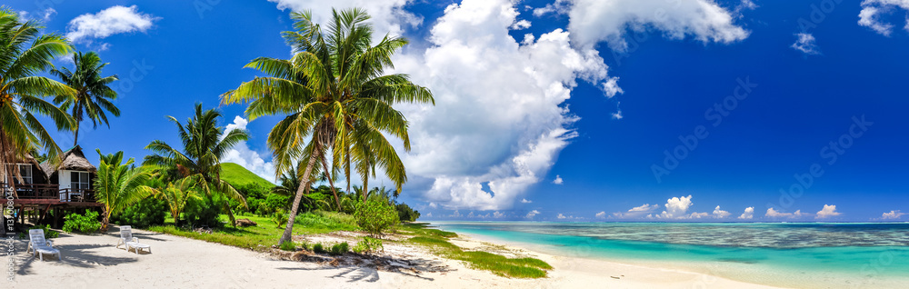 Fototapeta Stunning wide angle view of a beautiful beach on the remote island of Aitutaki, north of the main island Rarotonga, Cook Islands. White sand beach, shallow water, palm trees and a bungalow resort.