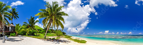Foto auf Gartenposter Strand Stunning wide angle view of a beautiful beach on the remote island of Aitutaki, north of the main island Rarotonga, Cook Islands. White sand beach, shallow water, palm trees and a bungalow resort.