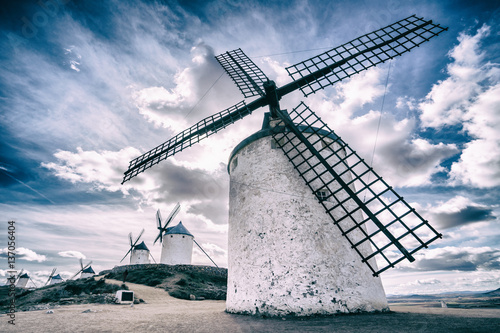 Fotografering  The windmill against the cloudy sky