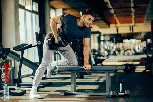 Fotografia  Young handsome man doing one-arm dumbbell back exercise on bench