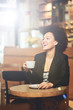 Mixed race, African American woman drinking coffee in cafe