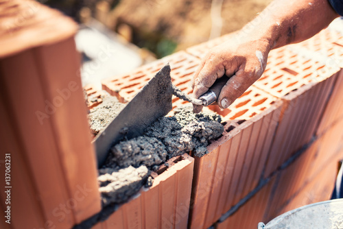 Foto op Aluminium Wand industrial details - Construction bricklayer worker building walls with bricks, mortar and putty knife.