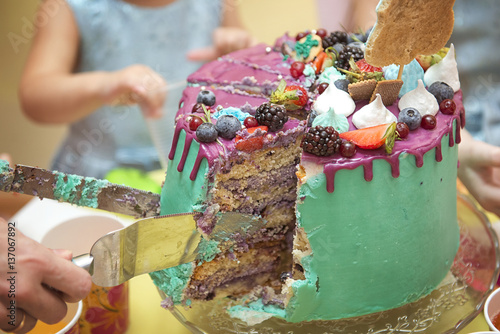 Birthday Cake Cut With A Knife Into Pieces With Bright Interiors