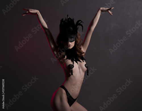 Plakat  Sexy slim woman, burlesque dancer, unrecognizable stripper in black mask and feathers