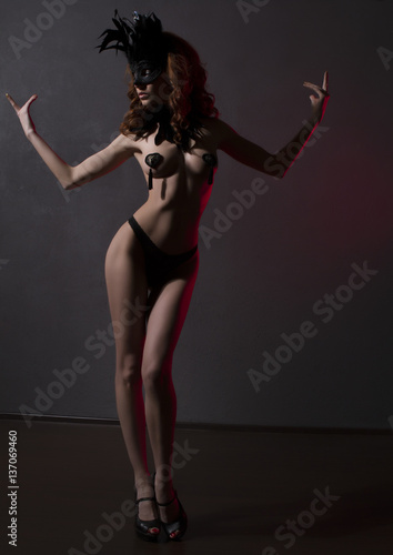 Photo  Sexy slim woman, burlesque dancer, unrecognizable stripper in black mask and feathers