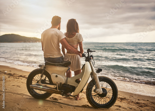 romantic couple sitting on vintage bike watching sunset at