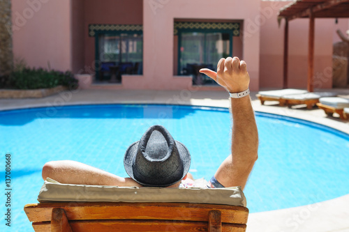 Obraz na plátne man in a hat lying on a lounger by the pool sun day