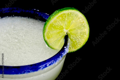 Fotografie, Obraz  Blue rimmed glass with margarita and lime slice against a black background