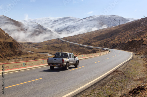 Obraz Pickup truck on the road, Beautiful winter road in Tibet under snow mountain Sichuan China - fototapety do salonu