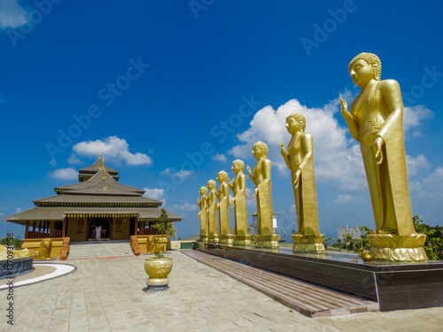 In de dag Bangkok Golden Temple Palace Relic House with series of golden Standing Buddha Statues bodhi tree lion statue scluptures with blue sky and clouds at Nelligala International Buddhist Center Kandy, Sri Lanka