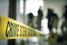 Crime Scene Tape With Blurred Forensic Law Enforcement Background In Cinematic Tone