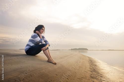 Papiers peints Detente Young woman sitting on sandbar at sunset