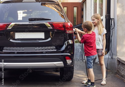 Brother and sister plugging charger to electric car