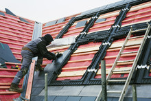 A Roofer Replacing The Tiles O...
