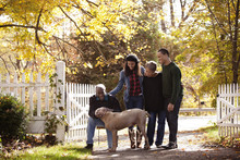Family At Driveway Gate With Dog