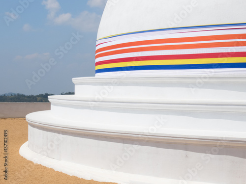 Three Rings Of White Stupa Dagabo On Sand Wrapped With Buddhist Flag And Blue Sky