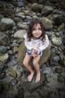 Girl (6-7) sitting on beach rock