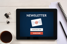 Subscribe Newsletter Concept On Tablet Screen With Office Objects On White Wooden Table. All Screen Content Is Designed By Me. Flat Lay