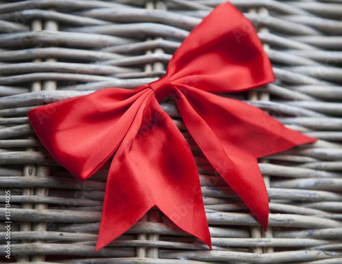 Fotografie, Obraz  nœud rouge cadeau sur fond de rotin