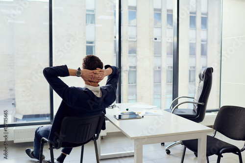 Deurstickers Ontspanning The concept of business success is a dream vacation relax. Young businessman hands behind his head resting in a modern office.