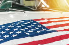 USA Flag On The Hood Of A White Car