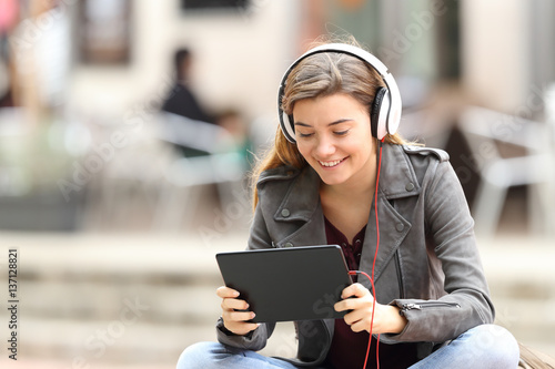 Girl learning on line with a tablet and headphones