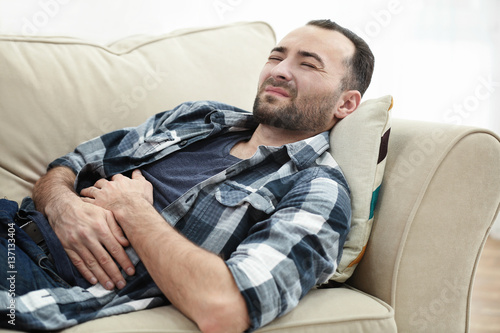 Handsome man suffering from stomach ache while lying on sofa at home Fototapeta