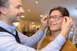 ophthalmologist and beautiful brunette female choosing glasses in optics store