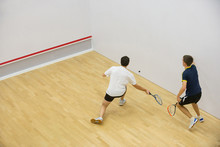 Squash Players In Action On Squash Court, Back View/Two Men Playing Match Of Squash.