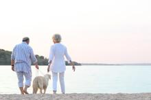 Senior Couple And Big Dog Walking On Riverside