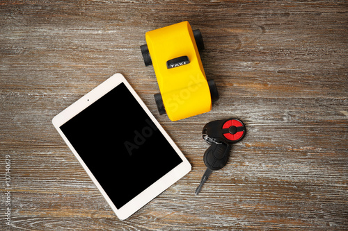 Deurstickers Oude auto s Yellow toy taxi with tablet and car key on wooden background