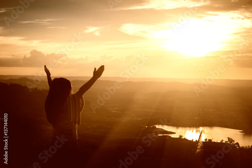 Girl arms raised to the sky, thank God.