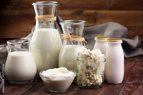 Aluminium Prints Dairy products milk products - tasty healthy dairy products on a table on: sour cream in a white bowl, cottage cheese bowl, cream in a a bank and milk jar, glass bottle and in a glass