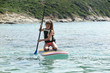 young girl learns to paddle on her knees to start